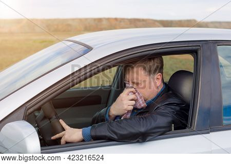A Man Driving A Car With A High Temperature Wipes His Snot With A Handkerchief.