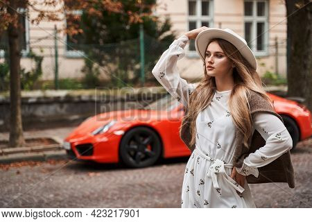 Beautiful Young Girl In Fashionable Stylish Dress And Hat Posing On Luxury Defocused Red Car Backgro