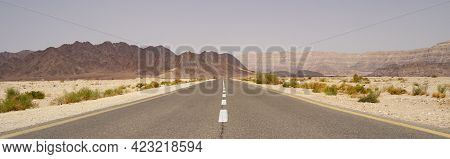 A Narrow Road Leading To Distant Mountains, In The Arava Desert In Israel.