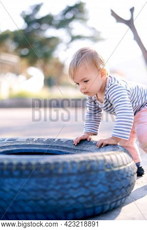 Child Stands And Leans On A Car Tire In A Parking Lot