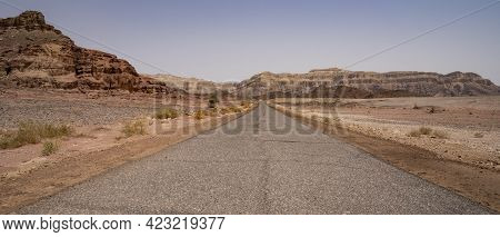 A Narrow Road Leading To Distant Mountains, In The Timna Valley Desert Park, Southern Israel.