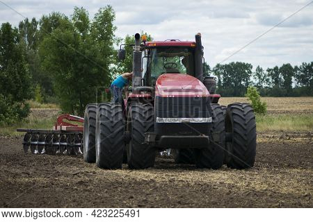 Tractor Driver Near A Large Red Tractor. A Farmer On A Tractor Prepares Land For A Seeding Tractor W