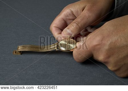 Hands Of A Man Winding An Old Gold Watch