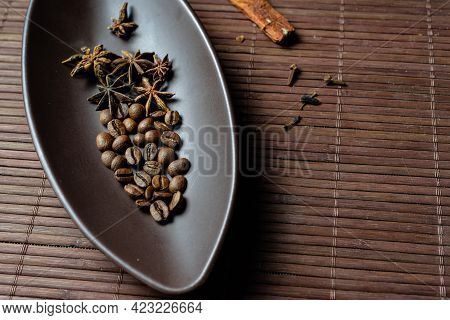 Brown Canoe-shaped Dish On Bamboo Mat With Coffee Beans, Star Anise, Cloves And Cinnamon .