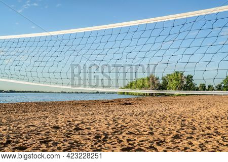 early summer morning in Boyd Lake State Park, Colorado with an empty swimming beach and volleyball net,  a popular boating and recreation destination in northern Colorado
