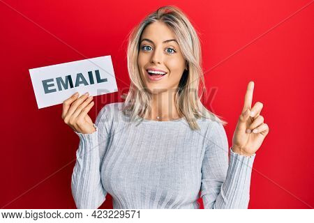 Beautiful blonde woman holding paper with email address smiling with an idea or question pointing finger with happy face, number one
