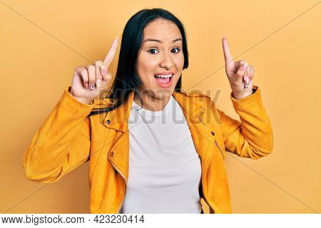 Beautiful hispanic woman with nose piercing wearing yellow leather jacket smiling amazed and surprised and pointing up with fingers and raised arms.