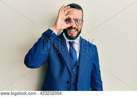Young man with beard wearing business suit and tie doing ok gesture with hand smiling, eye looking through fingers with happy face.