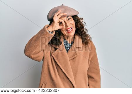 Middle age hispanic woman wearing french look with beret doing ok gesture with hand smiling, eye looking through fingers with happy face.