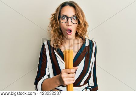 Young caucasian woman holding uncooked spaghetti pasta scared and amazed with open mouth for surprise, disbelief face