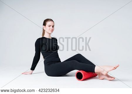 Cute Young Girl In Sportswear Sitting On The Floor In The Gym And Doing Exercise Using The Fascia