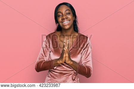 Young african american woman wearing sexy party dress praying with hands together asking for forgiveness smiling confident.
