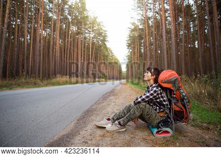 Tired Female Tourist Sits On The Side Of The Road With Huge Backpack And A Mat. Domestic Tourism, In