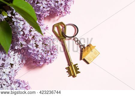 House Key With Keychain On Pink Spring Background And Lilac Branches. Summer Holiday Home, Booking C