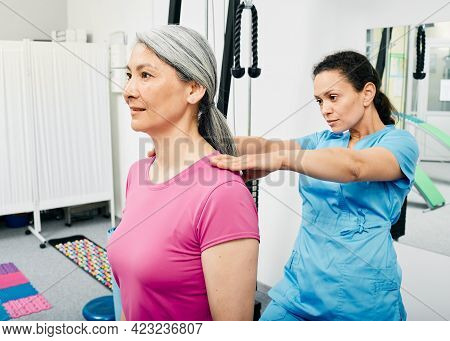 Osteopath Examines A Spine Of A Mature Woman. Medical Exam Of Scoliosis, Osteochondrosis At Rehab Cl