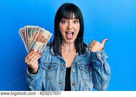 Young hispanic woman holding egyptian pounds banknotes pointing thumb up to the side smiling happy with open mouth