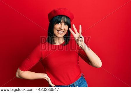 Young hispanic woman wearing french look with beret showing and pointing up with fingers number three while smiling confident and happy.