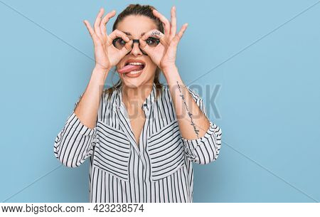 Young caucasian woman wearing business shirt and glasses doing ok gesture like binoculars sticking tongue out, eyes looking through fingers. crazy expression.