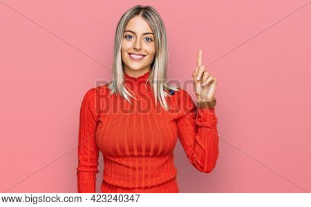 Beautiful blonde woman wearing casual clothes showing and pointing up with finger number one while smiling confident and happy.