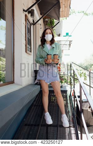 Stock Photo - Beautiful Girl In Mask  With Takeaway Coffee In A Cafe. Opening A Cafe. Work Cafe With