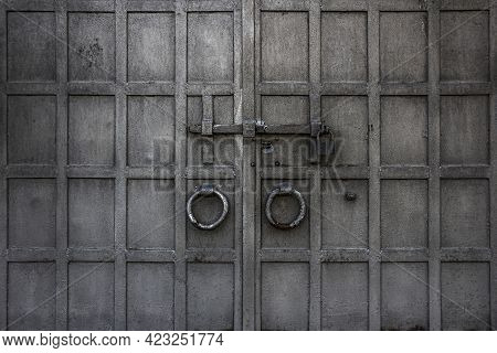 An Old Wrought Metal Gate With Handle, Doorknock, Deadbolt, Can Be Used As A Background