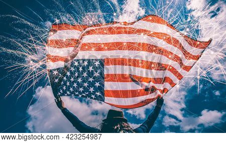 Young happy patriot girl holding the american flag under the 4th of July under fireworks.