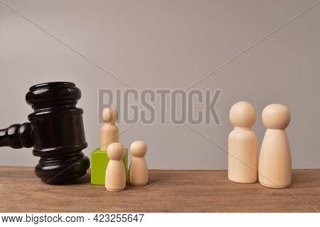 Wooden Doll Figures And Judge Gavel. The Concept Of Children Protection From The Criminal Offence.