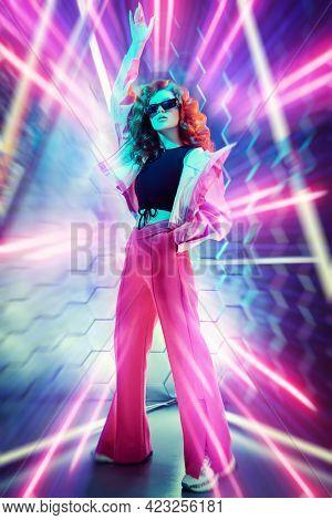 Hi-tech dance style. Beautiful young dancer girl dancing in neon light. Modern dances. Disco.