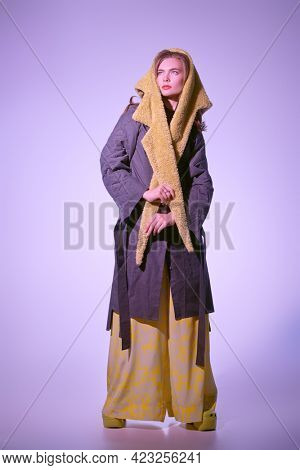 Haute couture clothing. Fashion model girl poses in stylish clothes from the spring-summer collection. Full length studio portrait.