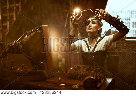 World of steampunk. Beautiful steampunk lady scientist inventor works in her laboratory with Victorian interior.