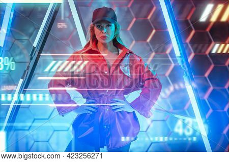 Techno style, disco. Stylish sexy woman in trendy red jacket and baseball cap posing in the light of neon lamps. Fashion shot.