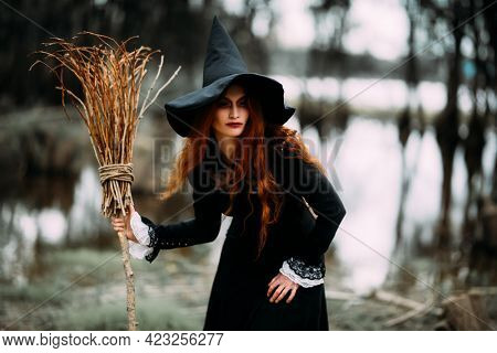 Halloween. A portrait of an angry witch with a broomstick near the forest. Magic, dark force, spell.