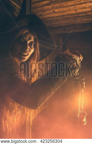 Redhead witch with a lantern near the wooden house. Halloween. Magic, dark force, spell.