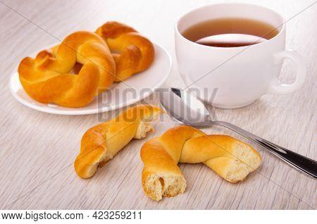 Two Wicker Buns In Shape Ring In White Plate, Cup Of Tea, Teaspoon, Broken Bun On Wooden Table