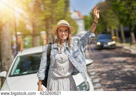 A person wearing a hat catching taxi.