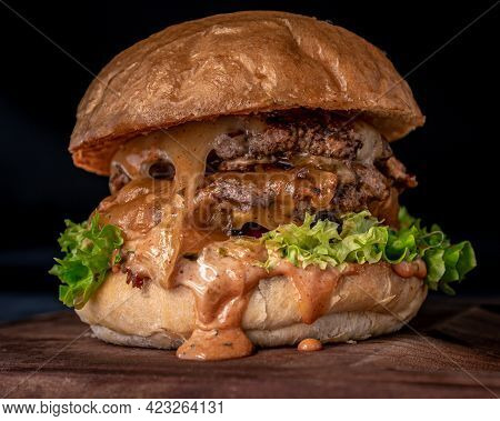 Tasty Double Beef Patty, Artisan Bun, Bacon, Jack Cheese, Cheddar Cheese And Pickle Dressing Served
