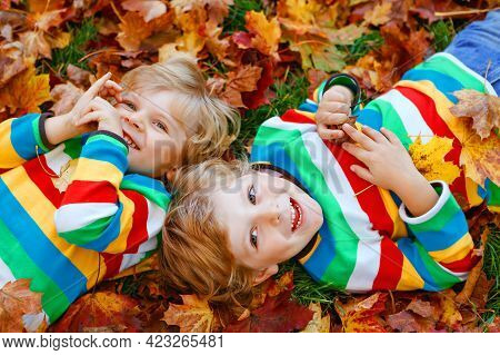 Two Little Twin Kids Boys Lying In Autumn Leaves In Colorful Fashion Clothing. Happy Siblings Having