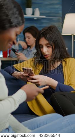 Group Of Mixed Race People Hanging Out Together Late At Night In Living Room Searching Online News O