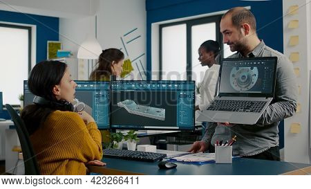 Engineer Holding Laptop And Pointing On Display Showing To Manager 3d Gears Image Working In Cad Pro