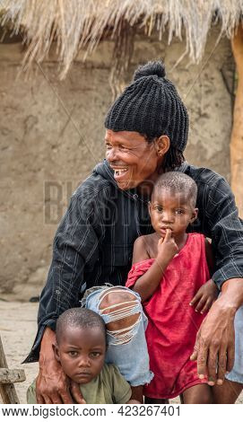 African family, father holding his children, yard in a village in Botswana
