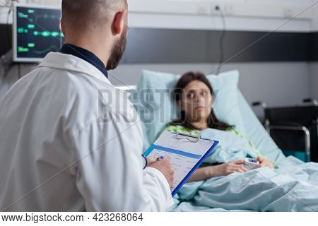 Specialist Physician With Stethoscope Writing Disease Treatment On Clipboard Checking Sickness Sympt