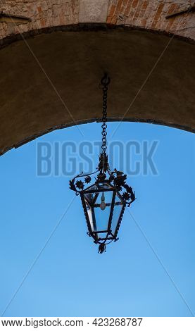 A Hanging Streetlight In An Archway In Lucca, Italy