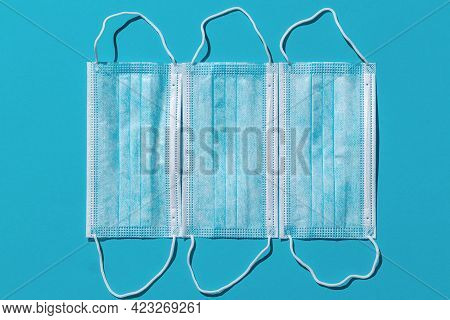 Three Medical Masks Isolated On A Bright Blue Background. Hard Shadows From The Sun At Noon With Cop
