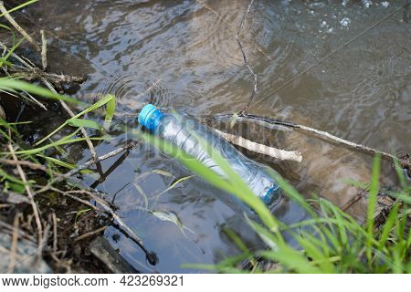 Plastic Bottle Floating In Water In Nature, Top View. Discarded Plastic Garbage In A Stream Lake Or