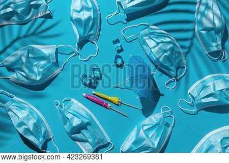 Pattern With Many Medical Masks, Ice Cubes And Beach Umbrellas Isolated On A Bright Blue Background.