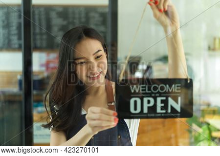 Portrait Of Female Barista Decorating Her Coffee Shop With The Label On Glass Door
