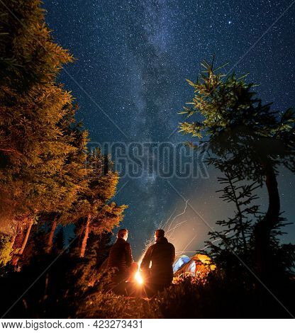 Back View Of Man And Woman Travelers Sitting Near Bonfire Under Beautiful Night Sky With Stars. Magn