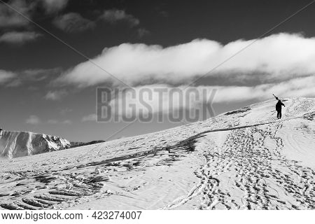 Skier With Skis On His Shoulder Go Up To Top Of Mountain In Cold Sun Day. Caucasus Mountains In Wint