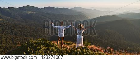 Back View Of Happy Couple In White Clothes Is Standing On Top Of Mountain. Woman And Boyfriend Are H