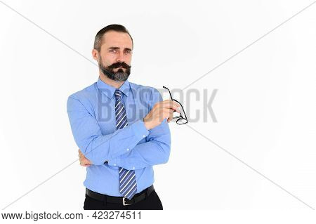 Portrait Of Confident Middle-aged Businessman In Blue Shirt And Holding Glasses With A Beard And Mus